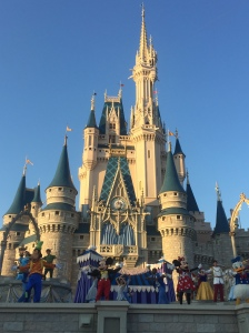 Disney characters dance in front of the castle.