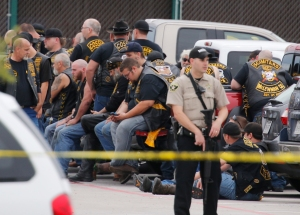 FILE - In this May 17, 2015 file photo, a McLennan County deputy stands guard near a group of bikers in the parking lot of a Twin Peaks restaurant in Waco, Texas. The prevailing images of protests in Baltimore and Ferguson, Missouri, over police killings of black men were of police in riot gear, handcuffed protesters, tear gas and mass arrests. The main images of a fatal gun battle between armed bikers and police in Waco, Texas, also showed mass arrests _ carried out by nonchalant-looking officers sitting around calm bikers on cell phones. (Rod Aydelotte/Waco Tribune-Herald via AP)